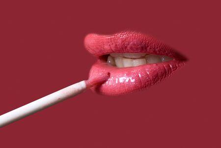 Sensual pretty woman applying cosmetics on her lips close-up shot on purple Stock Photo - 4297863
