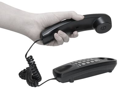 Communication on white. office black telephone with hands dialing.  photo