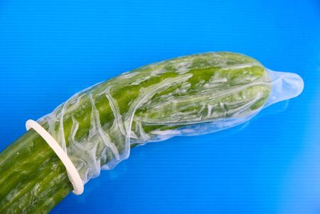 'phallic symbol': Cucumber in a condom ion blue white Stock Photo