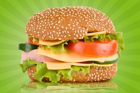 Burger with ham cheese tomatoes cucumbers and lettuce photo