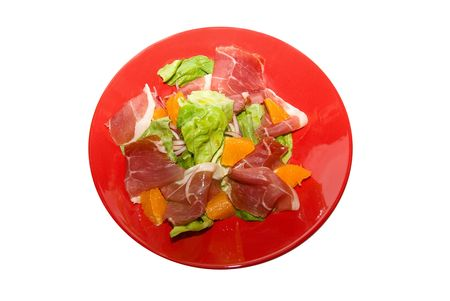 Salad: gammon with orange fruit and lettuce at red dish on white. It is very delicious. photo