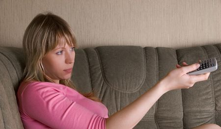 Girl sitting on the sofa and watching tv photo