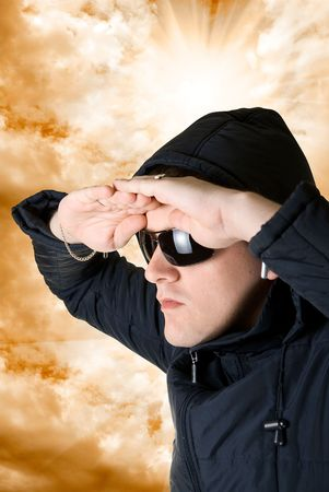 man look at distance in black sunglasses and jacket on orange sky background photo