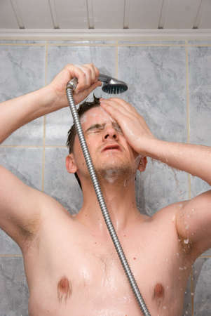 Man having shower in bathroom with soap and shampoo photo