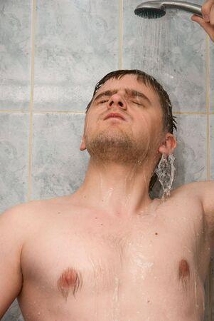 Man having shower in bathroom photo
