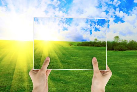 Hand holding photo of field of green grass on background with sunrise photo