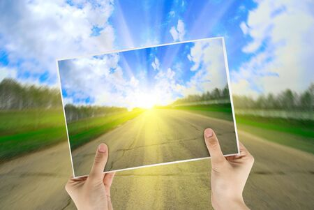 nature photography: Hand holding photo of road background with sunrise Stock Photo