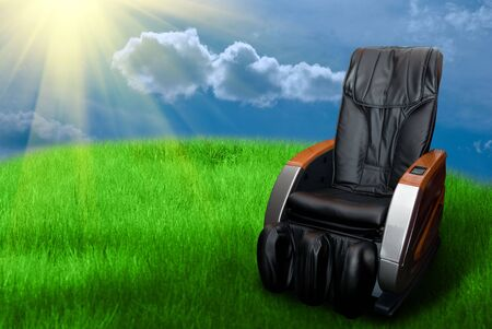 Sunny day with massage arm-chair on the grass field    Stock Photo