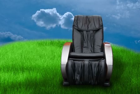 massage arm-chair on the green grass field background.    photo