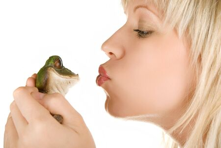 Frog prince being kissed by a beautiful blond girl isolated on white