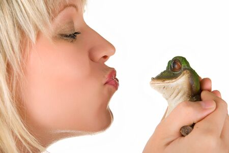 Pretty young blond woman kissing a frog isolated on white photo