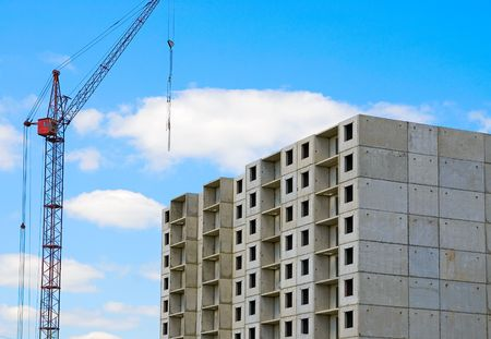 housing development: Construction crane and home on blue sky background