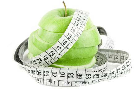 Measuring tape wrapped around green sliced appleisolated on white   Stock Photo
