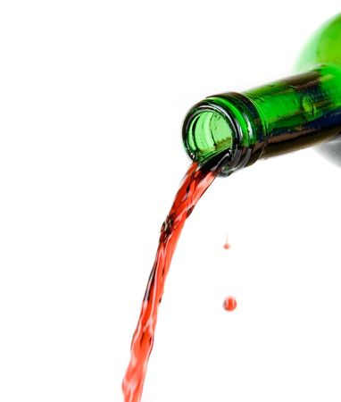 Wine being poured from a bottle isolated on white background photo