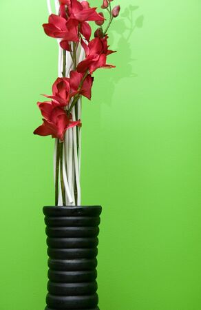 vase and flowers on green background photo