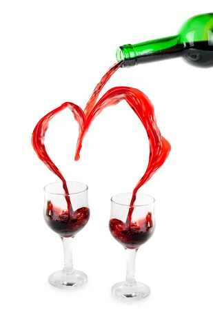 Heart from pouring red wine in goblets isolated on white photo