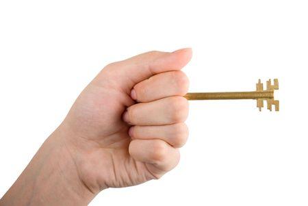 Fingers holding Golden key isolated on white background photo