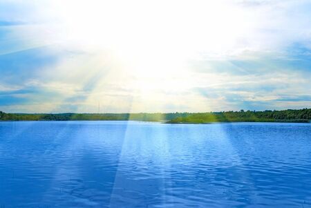 Lake, green field, sun and blue sky photo