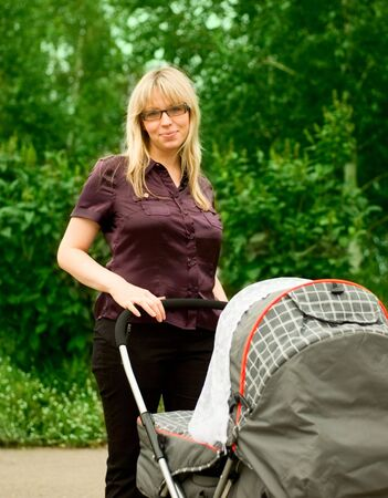 mother with pram walking in a city park Stock Photo - 5345453