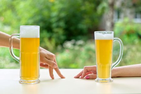 two human hands, man and woman with beer in glass.  Resting man and woman.  photo