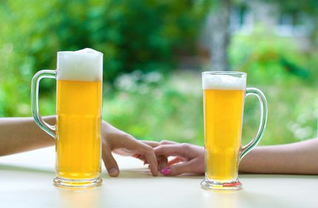 two human hands, man and woman with beer in glass. Stock Photo - 5545681