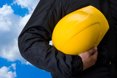 Yellow helmet at man hands on blue sky background photo