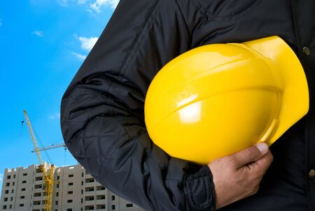 Closeup  of Yellow helmet at builder hands on building background Stock Photo - 5616022