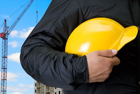 Closeup  of yellow helmet at builder hands on building background photo
