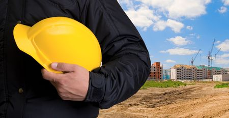 building safety: Closeup  of yellow helmet at builder hands on building background