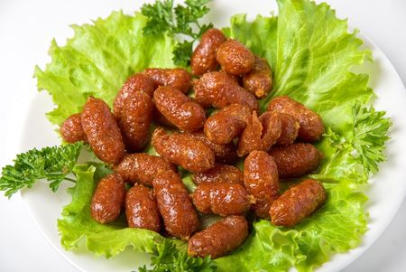 roasted tasty sausages on green lettuce with isolated on white photo