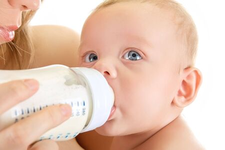 Mother give drink her baby boy by feeding bottle photo