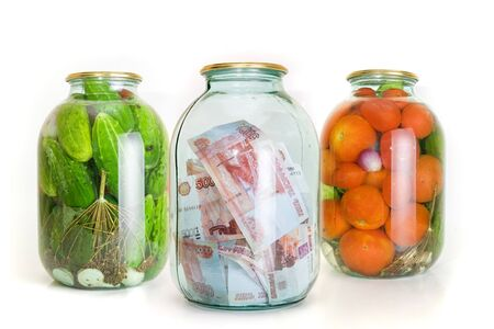 Glass jars with cucumbers tomatoes and money on a white background Stock Photo - 5933911