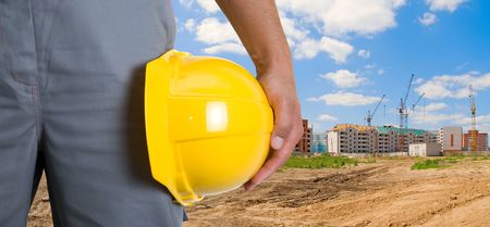 Closeup  of yellow helmet at builder hands on building background Stock Photo - 6017255