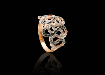 Beauty gold ring with diamond gems on black background photo