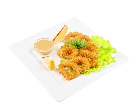 Deep-fried squid with salad leaves, sauce, green and lemon on a white background photo