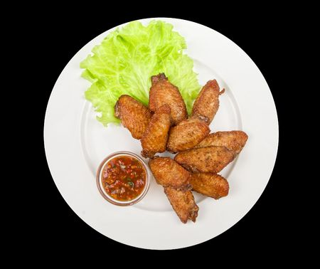 chicken roasted wing dish with sauce on a black background photo