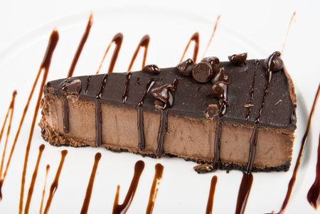 chocolate cake on a white plate drizzled with chocolate sauce   photo