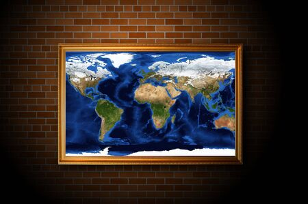 frame with earth map hanging on the brick wall photo