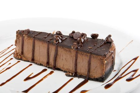 eating chocolate: chocolate cake on a white plate drizzled with chocolate sauce