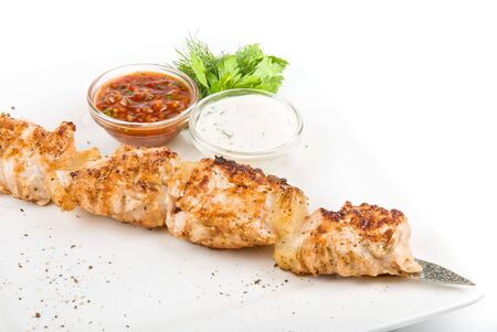 Grilled chicken kebab with sauce and greens on white plate Stock Photo - 6357466