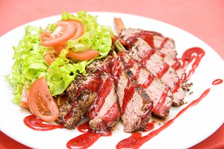 Roasted Beef meat at cranberries sauce with vegetables photo