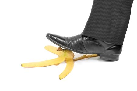 Business boot to step on a banana skin on a white photo
