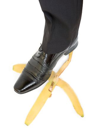 Business boot to step on a banana skin on a white Stock Photo - 6417431