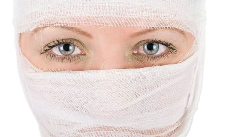 woman with bandages on her face closeup on white photo