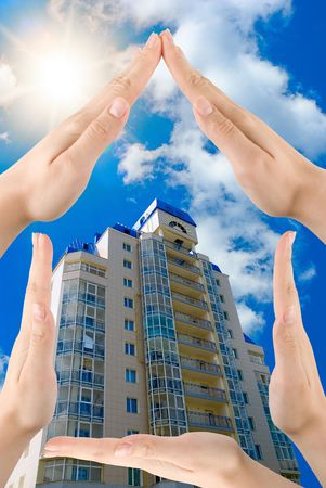 Hands showing home sign on blue modern building background Stock Photo - 6496707