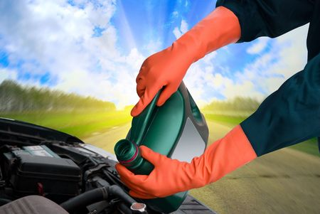 oil tool: man pours motor oil into the engine