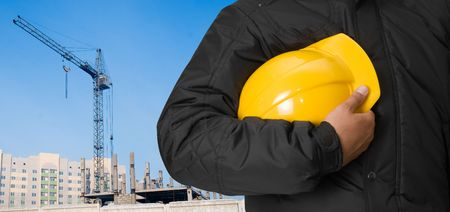 Closeup of builder with yellow helmet on building panorama background photo