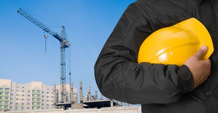 Closeup of builder with yellow helmet on building panorama background Stock Photo - 6552226