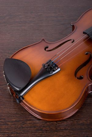 classic violin closeup on a brown wooden background photo