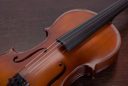 violin closeup on a brown wooden background photo